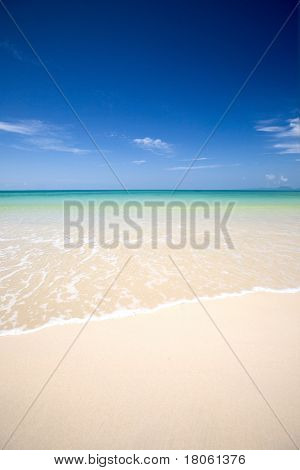 Crystal clear waters of the Andaman sea with soft white sand and clear blue sky.