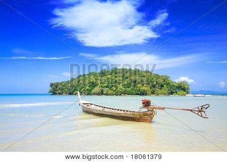 A lone tailboat waits by the shore for the tide to come in at Krabi bay, Thailand, with clear blue water against blue skies.