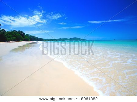 Beautiful beach with crystal clear blue waters of the Andaman sea against blue sky at Krabi bay, Thailand.