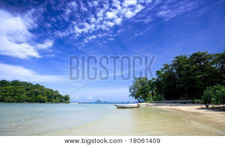 A lone tailboat by the shore  at Krabi bay, Thailand, with clear blue water against blue skies.