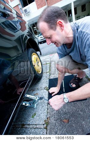 Man changing his tyre as he suffers from a puncture