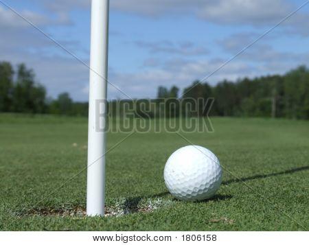 Bola de golfe ao lado do furo