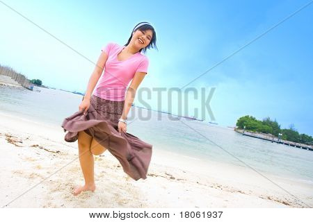 Young and happy Asian female dancing on a tropical beach