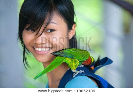 An Orange-winged Amazon parrot  perched on a young girl's shoulder, curious over her rucksack.