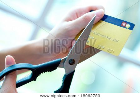 A credit card being cut by big pair of scissors