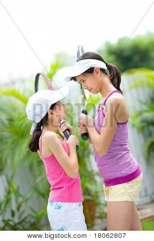 Two sporty sisters face to face before a game of tennis