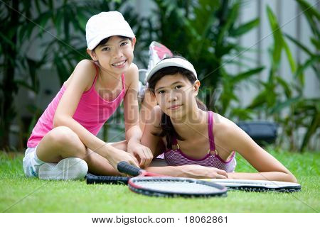 Two teenage sisters in tennis outfit, with rackets, outdoors