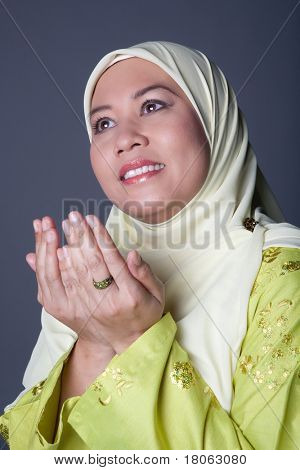Muslim woman with both palms together in gesture of praying.