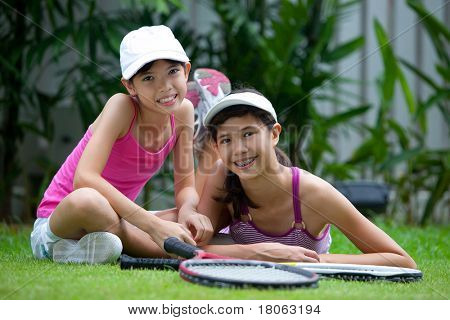 Two sisters in tennis outfit with rackets, outdoor.