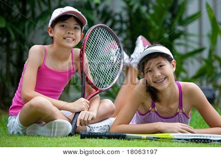 Two sisters in sporty clothes enjoying time outdoor together