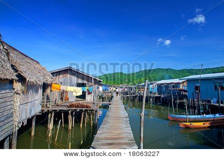 Wooden boardwalk leading to thatched roof homes of a water's village in Tuaran, Sabah Malaysia.