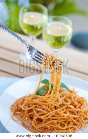 Plateful of spaghetti in tomato sauce in an outdoor setting.