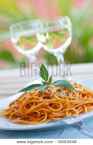 Plate of spaghetti with tomato sauce in an outdoor setting.