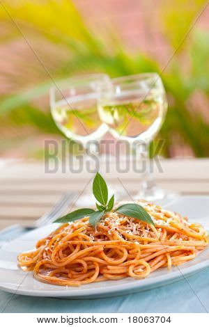 A plate of spaghetti with tomato sauce and two glasses of wine in background.