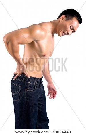 Man grimaces as he suffers from pain on lower back.