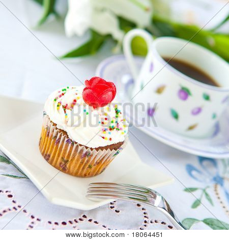 Pretty cupcake with a cup of coffee
