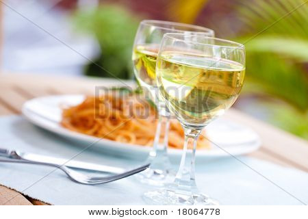 A serving of spaghetti in tomato sauce with two glasses of white wine