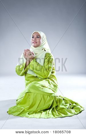 Beautiful Muslim woman in praying pose showing thankfulness and gratification.