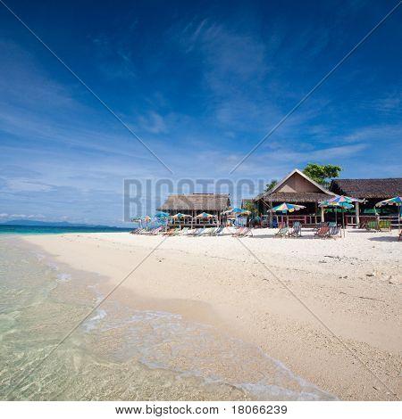 Idyllic tropical island getaway with sunbeds on white sandy beach