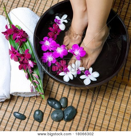 Feminine feet in orchid spa bowl with hot stones