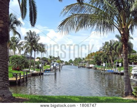 Tropical Homes On Canal With Boats