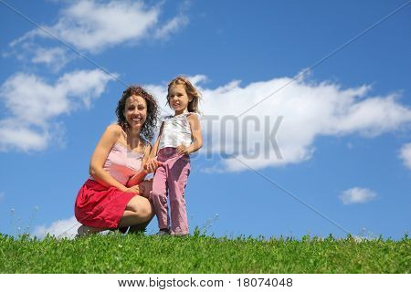 Mother squatting alongside with daughter holds it for hand and laughs