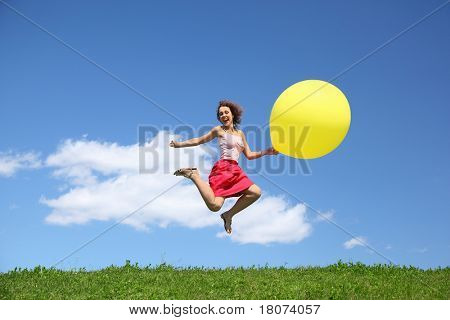 Woman jumps away from grass with large inflatable ball and laughs on wing