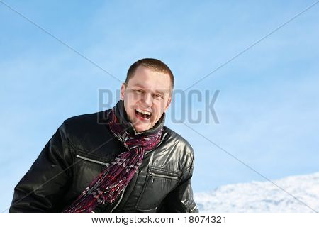 Young man laughs merrily in day-time in street in winter