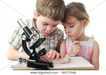 Curious little boy and girl draw diagram near black microscope