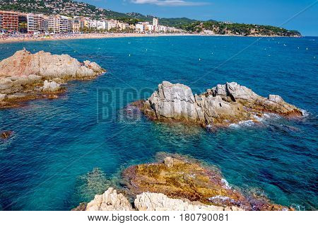 panoramic view of seashore with rock cliff and a town on background in Lloret de Mar, Catalonia, Costa Brava, Spain