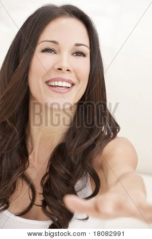 Portrait of a beautiful brunette young woman in white t-shirt laughing and reaching out
