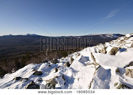 Taiga forest in Russia. Rocky slope of mountain. National park Taganay. South Ural mountains.