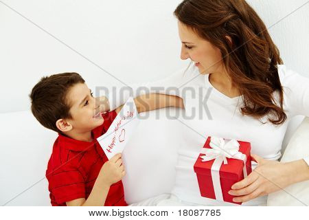 Cute lad with congratulating card looking at his mother with giftbox