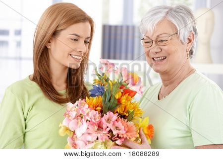 Elderly mother getting flowers from young daughter at mother's day, both smiling.?
