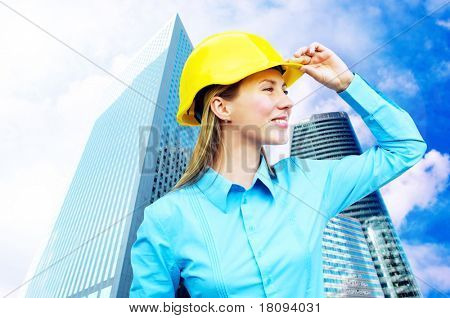Young architect-woman wearing a protective helmet standing on the building background