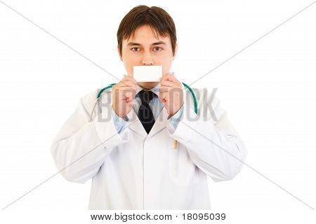 Medical doctor holding blank business card in front of mouth isolated on white