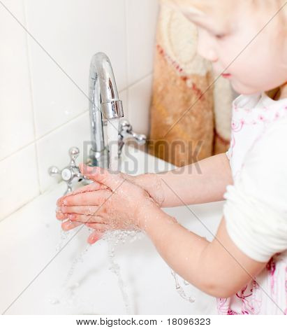 Little girl washing her hands in bathroom, shallow focus