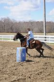 foto of barrel racing  - A young woman turns around a barrel and races to the finish line - JPG
