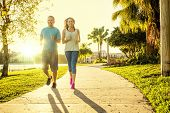 Man and woman exercising and jogging together at the park. Happy and smiling as they run along the p poster