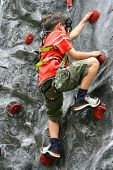 stock photo of climbing wall  - Young boy climbing up the indoor rockclimbing wall - JPG