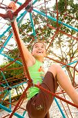 picture of spider web  - Active young girl climbing the spider web playground activity in summer - JPG