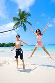 Brother and sister jumping up high while having fun at the sandy beach