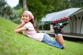 image of young girls  - Beautiful young girl resting after rollerblading in the park - JPG