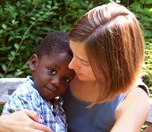 picture of babysitting  - young caucasian woman holding a young african american child - JPG