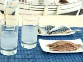 stock photo of ouzo  - Ouzo and misc seafood near the beach - JPG