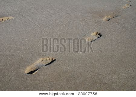 A line of human footprints in the sand on the beach at Folkestone in Kent, England.