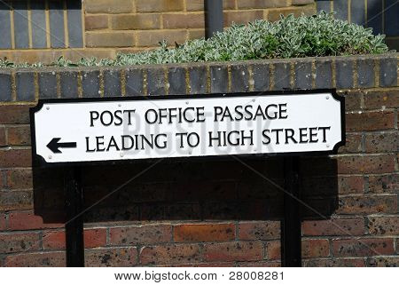 A street direction sign pointing to Post Office Passage in Hastings, East Sussex, England.