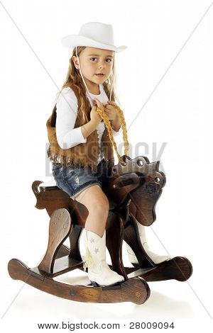 "An adorable kindergarten ""cowgirl"" sitting ready to ride a wooden rocking horse.  On a white background."