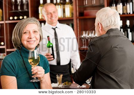 Wine bar senior couple enjoy drink smiling barman discussing
