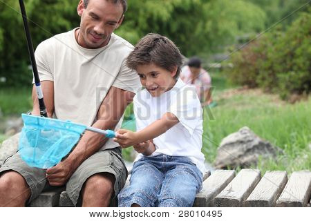 father and son enjoying fishing party by riverside